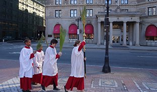 Acolytes process around Copley Square waving palms.