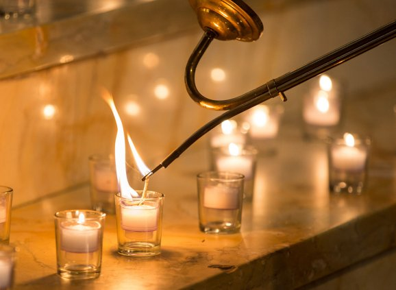 Votive candles being lit