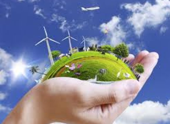 a hand holding a green earth with wind turbines.