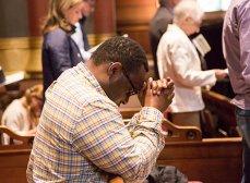 Man praying in pew
