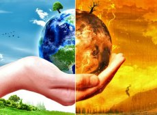 a hand holding the earth, one half green and happy, the other half on fire