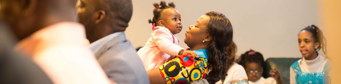 A mother smiles at her child during the Nigerian Christian Fellowship meeting.